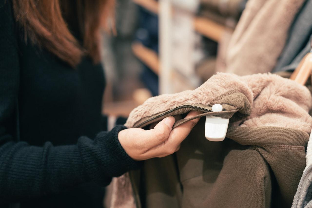 consumidor em loja de roupas olhando casacos